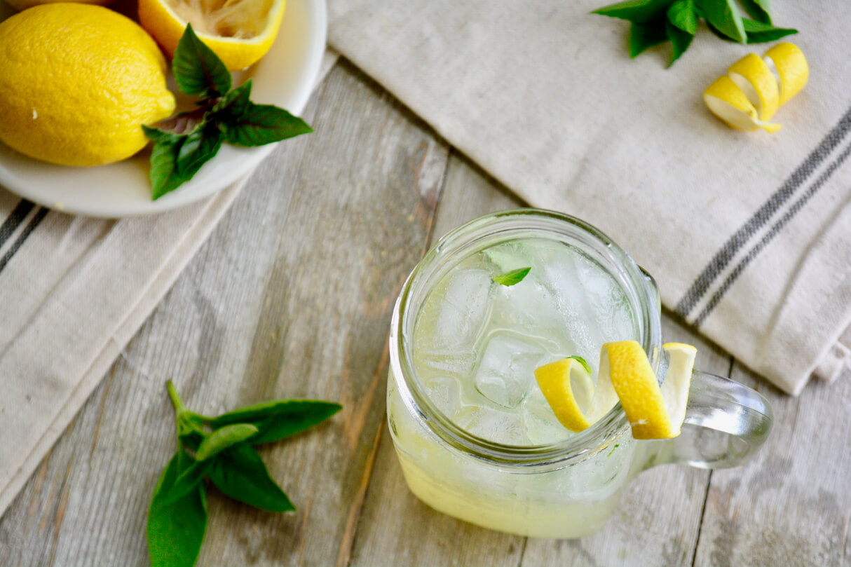 Birds eye view of a mason jar filled with basil lemonade on ice with a lemon peel curl on the rim and basil leaves mixed inside. The jar is surrounded by two sprigs of basil in the upper right and bottom left corners with a plate of cut lemons and basil sprig in the upper left corner. All items sit atop rustic whitewashed boards and a linnen sepia napkin with blue stripes on the end.