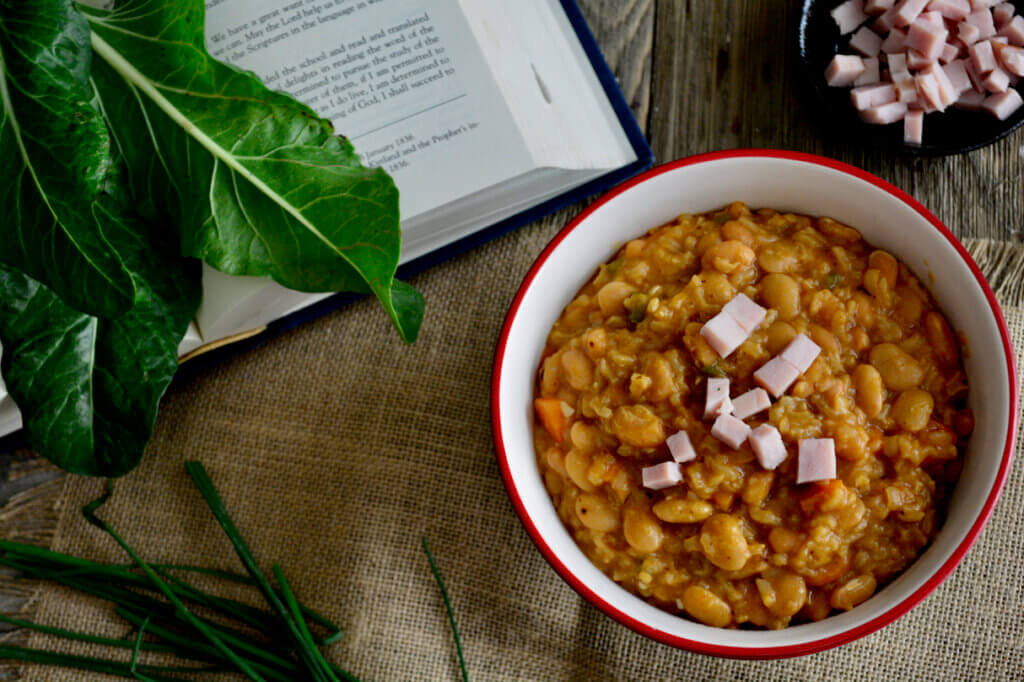 A bowl of ham and beans sits on top of wood and burlap in the lower right hand quadrant of the picture. In the upper right hand corner a small black dish is filled with additional cubed ham for garnishing. To the left of the bowl a book lays open with collard green leaves resting on top of the pages and chive sitting below the book.