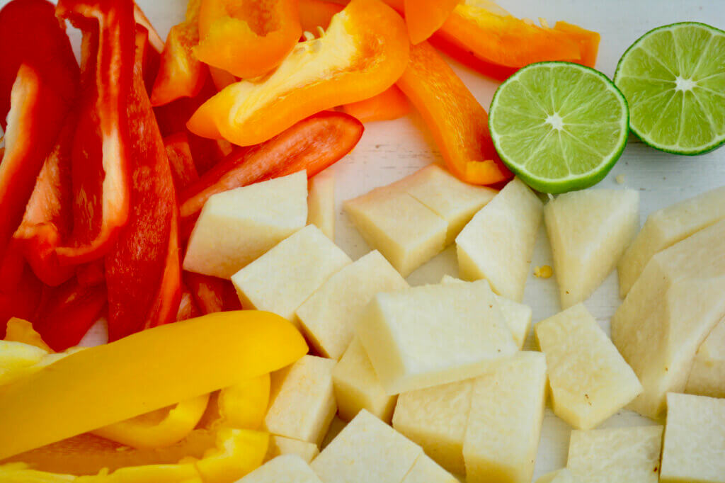 Chopped vegetales sit atop a white cutting board. Red, yellow, and orange bell pepper strips fill the left third of the image while cubed jicama takes up the lower right corner. Peaking out from the top right corner are two halves of a bright green lime.