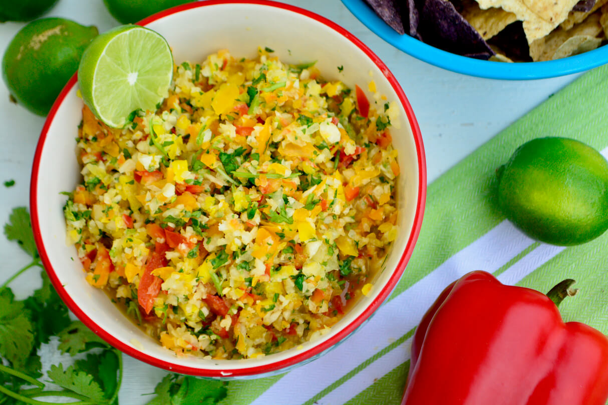 A orange trimmed, white interior bowl filled with multi-colored pico de gallo sits in upper left half of the picture. Limes, cilantro, and a red pepper are scattered around the bowl which sits atop a white and green striped cloth. A light blue bowl of yellow and blue corn chips sneaks out of the top right corner.